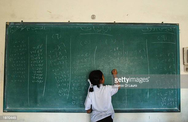An Iraqi female student writes on a blackboard on the first day back to a Christian school May 3 2003 in Baghdad Iraq Approximately 120 female...