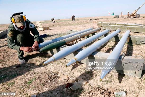 An Iraqi fighter from the Abbas Brigade which fights under the umbrella of the Shiite popular mobilisation units prepares ammunition as they fire...