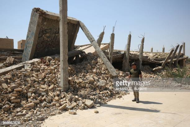 An Iraqi fighter from the Hashed alShaabi checks the severely damaged tomb of the late Iraqi dictator Saddam Hussein in the village of AlAwja on the...