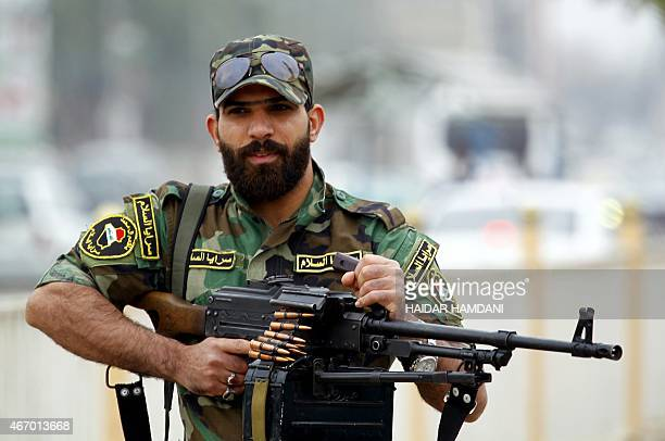 An Iraqi fighter from the Saraya alSalam a group formed by Iraqi Shiite Muslim cleric Moqtada alSadr holds his weapon as they gather with Iraqi...