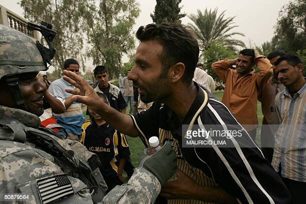 An Iraqi fighter shares a joke with a US soldier from 3rd Battalion 320th Field Artillery Regiment while waiting to be registered by the US military...