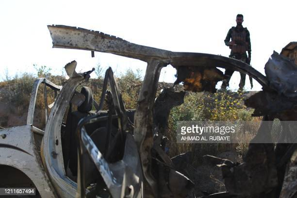 An Iraqi fighter with the Hashed al-Shaabi inspects the site of the Islamic State group attack, a day earlier, on a unit of the paramilitary force in...