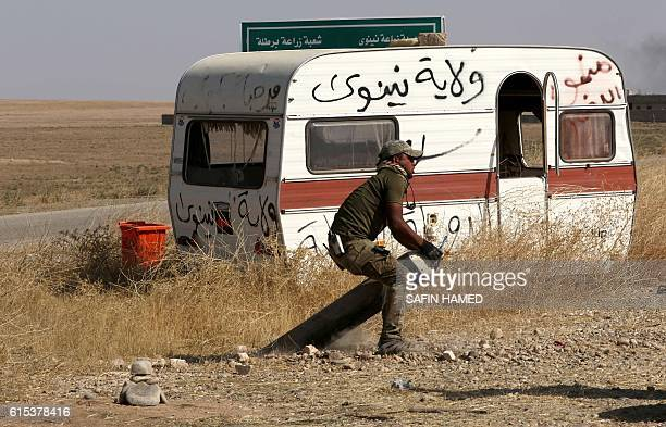 An Iraqi fighter works on detonating a landmine on October 18 2016 planted by the Islamic State group jihadists next to the village of Shaqouli about...
