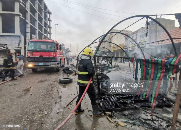 An Iraqi firefighter douses a fire amid clashes between anti-government protesters and supporters of firebrand Shiite cleric Moqtada Sadr, in the...