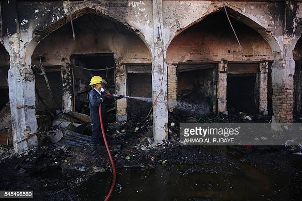 An Iraqi firefighter extinguishes fire at a market near the Sayyid Mohammed shrine in the Balad area located 70 kilometres north of Baghdad on July 8...