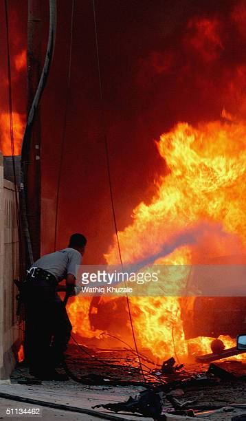 An Iraqi fireman battles the flames at the scene of a car bomb targeting a church in the Karradah district on August 1 2004 in Baghdad Iraq Car bombs...