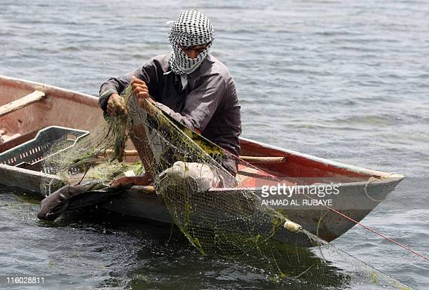 An Iraqi fisherman pulls in his nets on the al-Huwaiza marshes northern Amara, 420 km south of Baghdad on June 13 considered to be the demarcation...