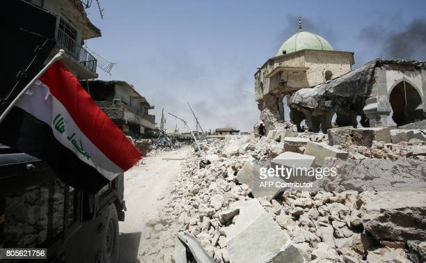 TOPSHOT An Iraqi flag waves as it hangs outside a CounterTerrorism Service humvee driving past the destroyed AlNuri Mosque in the Old City of Mosul...
