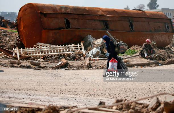 TOPSHOT An Iraqi fleeing her home in Mosul's old city walks past a damaged vehicle as she leaves the fighting area on March 30 due to the ongoing...