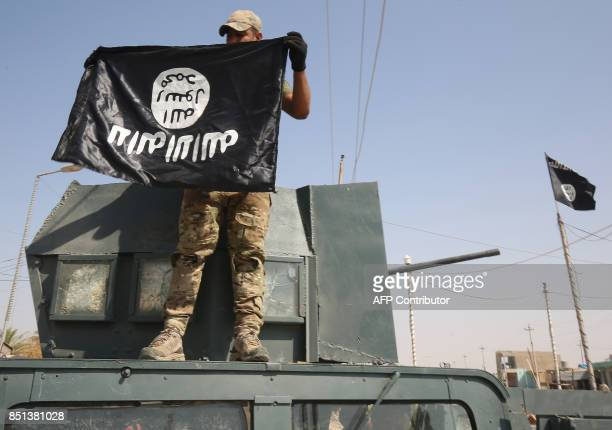 An Iraqi forces' fighter holds upside down an Islamic State group flag as he stands on a humvee in the northern Iraqi town of Sharqat on September 22...