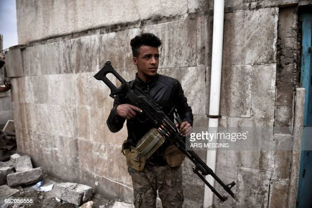 An Iraqi forces member holds a machine gun in west Mosul on March 11 2017 as the ongoing battle to retake the city from the Islamic State jihadists...