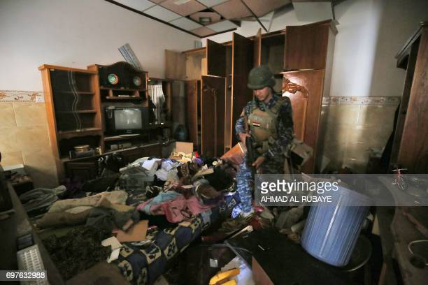An Iraqi forces member inspects a building as they advance towards the Old City of Mosul on June 19 2017 during an ongoing offensive to retake the...