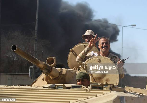 An Iraqi forces' officer flashes the victory gesture from the turret of an armoured vehicle during the advance through the town of Tal Afar, west of...