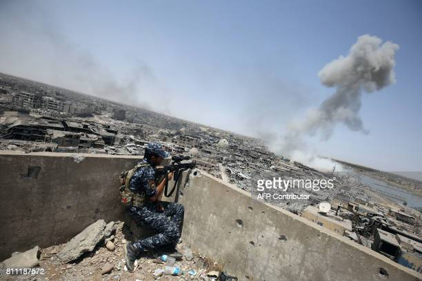 TOPSHOT An Iraqi forces sniper looks on as smoke billows following an airstrike by USled international coalition forces targeting Islamic State group...