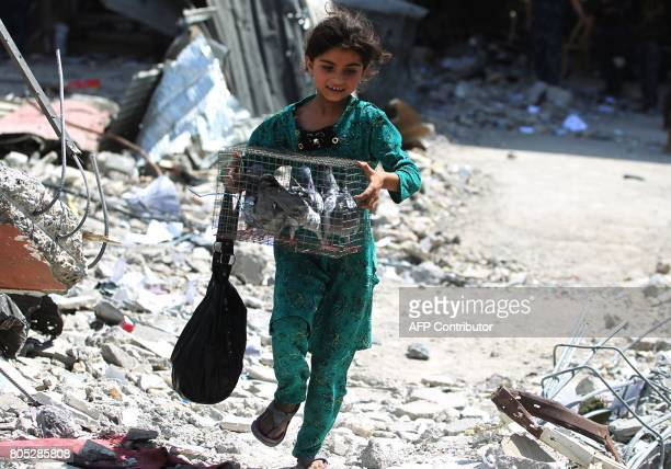 An Iraqi girl carries a bird cage as she evacuates her home in the Old City of Mosul on July 1 2017 where Iraqi forces are battling some of the last...