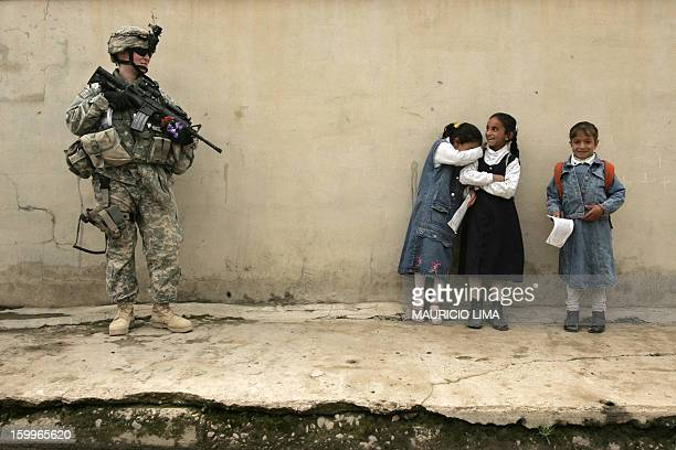 An Iraqi girl gets embarrassed after offering flowers to a US female soldier from Alpha Company 2nd Battalion 7th Cavalry Regiment during a joint...