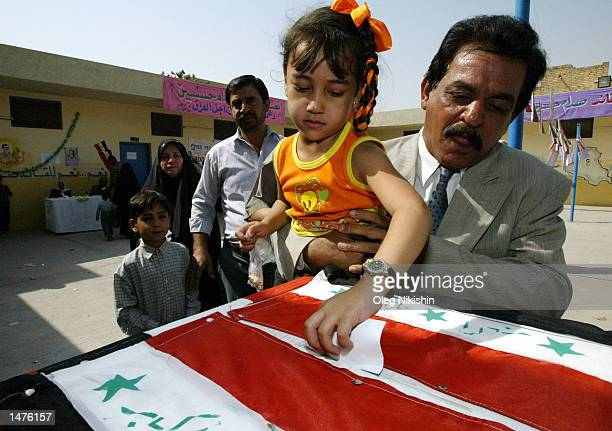 An Iraqi girl helps her father cast a ballot during a presidential referendum October 15 2002 in Baghdad Iraq Iraqi President Saddam Hussein is...