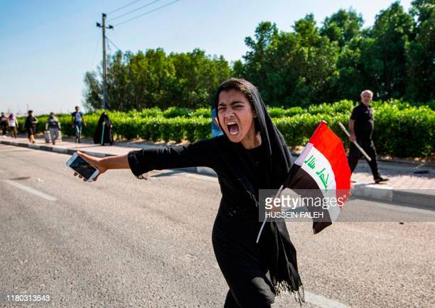 TOPSHOT An Iraqi girl holding a national flag chants slogans as she holds her cell phone in her hand during a demonstration outside the southern port...