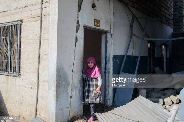 An Iraqi girl plays in the ruins of a primary school destroyed by Coalition airstrikes in Hay Al Malyah a neighbourhood of eastern Mosul liberated by...