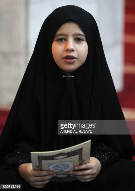 An Iraqi girl reads a copy of the Koran as he attends a reading class at the Sheikh Abdul Qadir aljailani mosque in central Baghdad on June 13 2016...