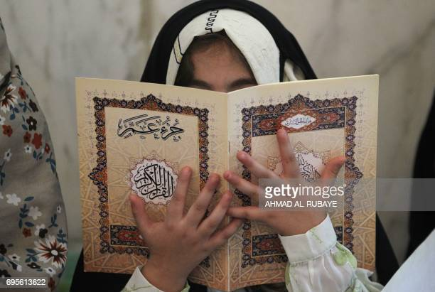 TOPSHOT An Iraqi girl reads a copy of the Koran as he attends a reading class at the Sheikh Abdul Qadir aljailani mosque in central Baghdad on June...