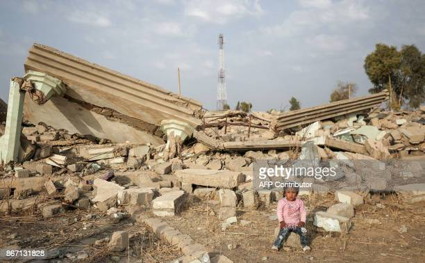 An Iraqi girl sits by the rubble of her home in the village of Barzan in the Zummar area of Nineveh province northwest of Mosul on October 27 2017...