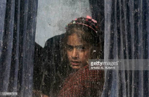 An Iraqi girl sits in a bus transporting displaced families from the displaced persons camp in Habbaniyah in Iraq's Anbar province on November 10,...