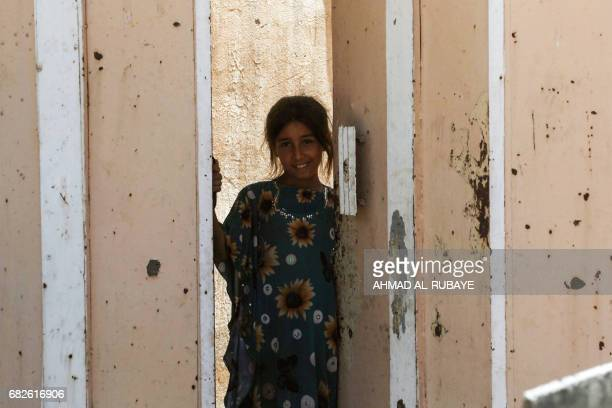 An Iraqi girl smiles at her door in western Mosul's al-Islah al-Zaraye neighbourhood on May 13, 2017 during a government forces' military offensive...