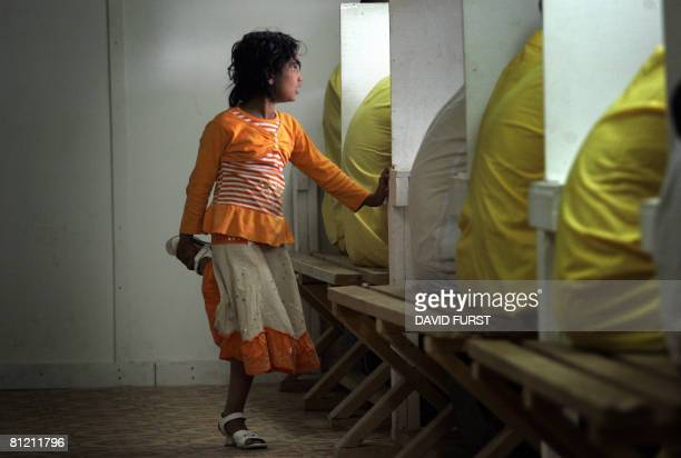 An Iraqi girl stands beside her father during his visitation time with his family inside the Camp Bucca detention centre located near the KuwaitIraq...
