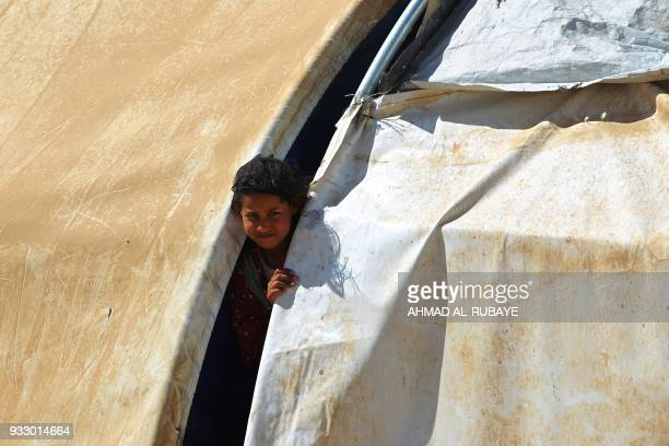 An Iraqi girl stands in the door of her tent in the displaced persons' camp in Tikrit on March 16 2018 / AFP PHOTO / AHMAD ALRUBAYE