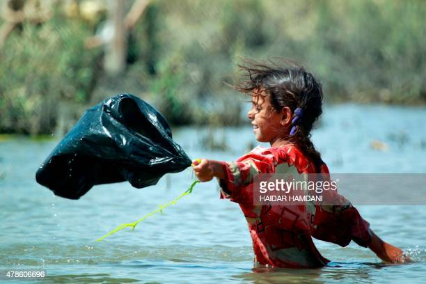 An Iraqi girl stands inside water in the Chibayish marshes near the southern Iraqi city of Nasiriyah on June 25, 2015. Marsh areas in southern Iraq...