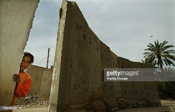 An Iraqi girl stands near a blast wall on April 22 2007 in the Karrada neighborhood of Baghdad Iraq US troops are building a wall that the military...