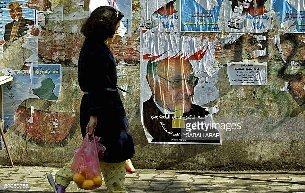 An Iraqi girl walks in front of torn election posters of Sunni Muslim candidate Adnan Pachachi pasted on a Baghdad wall 23 January 2005 in Baghdad...