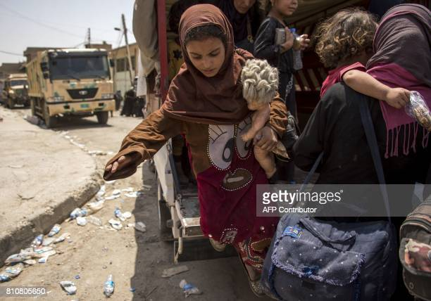 An Iraqi girl who fled the fighting between government forces and Islamic State group jihadists in the Old City of Mosul holds a doll in her arm as...