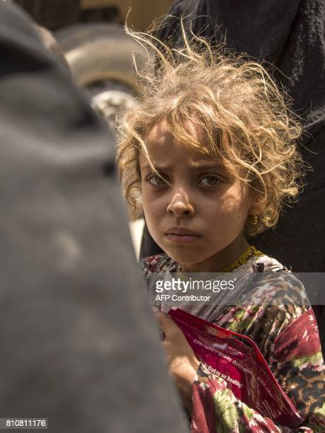 An Iraqi girl who fled the fighting between government forces and Islamic State group jihadists in the Old City of Mosul looks towards the camera in...