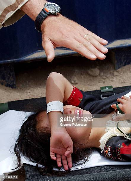 An Iraqi girl who was treated for illness by the US military is shielded from the sun before being reunited with her family in Camp Bucca April 27...