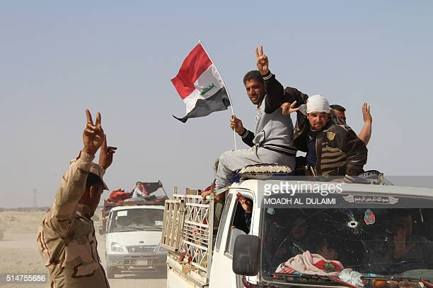 An Iraqi government forces member flashes the sign for victory as he guides pick up trucks evacuating civilians to a safe area on March 10 2016 after...