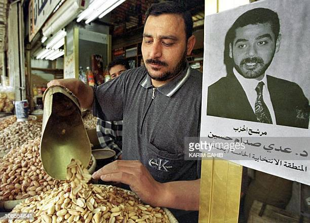 An Iraqi grocer sells peanuts with a portrait of President Saddam Hussein's son Uday hanging on his shop in downtown Baghdad 25 March 2000 Uday is...