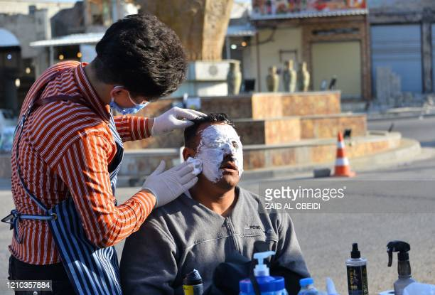 An Iraqi hairdresser, wearing personal protective equipment, provides a facial mask to a member of the security forces during the coronavirus...