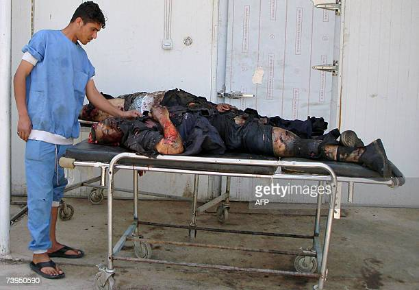 An Iraqi hospital worker inspects bodies outside the morgue of a hospital in the restive Iraqi city of Baquba northeast of Baghdad 23 April 2007 The...