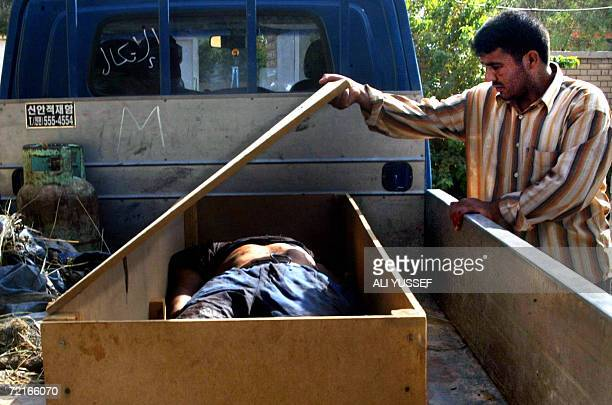 An Iraqi hospital worker inspects the body of a victim outside the morgue of a hospital in the restive city of Baquba northeast of Baghdad 14 October...