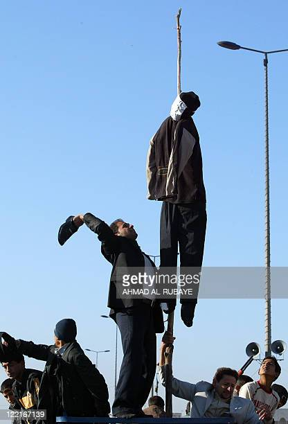 An Iraqi in the Shiite-majority Baghdad suburb Sadr City uses a shoe to beat an effigy of ousted dictator Saddam Hussein hanging from a rope as they...