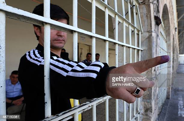 An Iraqi inmate shows his inkstained finger after casting his ballot at a prison in Arbil the capital of the autonomous Kurdish region of northern...
