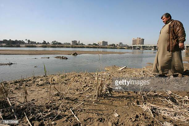 An Iraqi inspects the falling level of water of the Tigris River crossing in central Baghdad 07 January 2008 Parts of Iraq are in the grip of a...