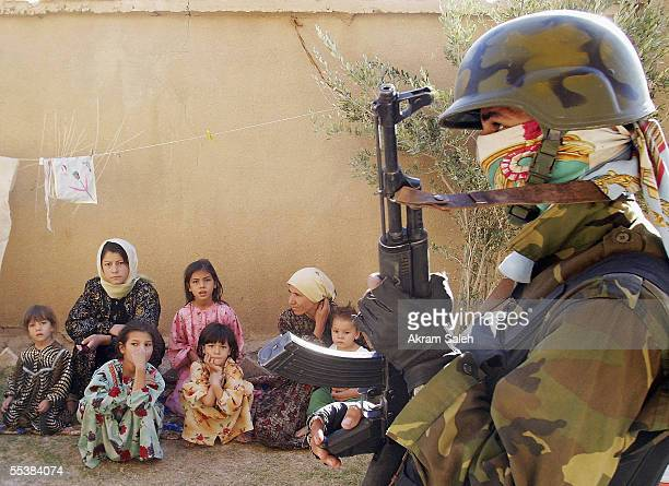 An Iraqi Interior Ministry commando of alBarq Brigade stands guard as an Iraqi family sit in their house during housetohouse searches September 12...