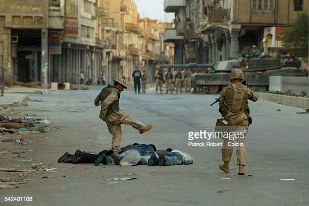 An Iraqi interpreter working with the US Marines patrolling the center of Baghdad kicks a looter until he is stopped by the order 'You're a fucking...