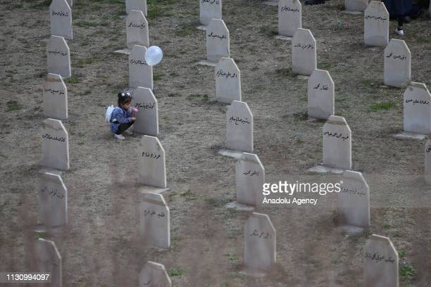 An Iraqi kid is seen near gravestones of people, who lost their lives on Halabja chemical attack staged on 16 March 1988, at Halabja cemetery in...