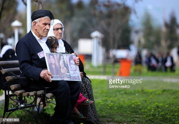 An Iraqi Kurd family holds images of loved ones as they visit in a grave yard for the victims of a gas attack by former Iraqi president Saddam...
