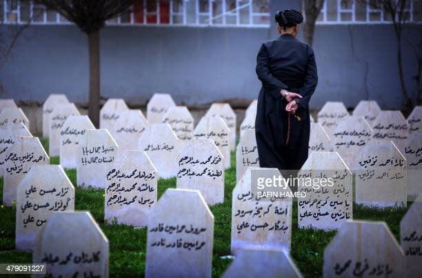 An Iraqi Kurd man visit at a grave yard and a monument for the victims who were killed in a gas attack by former Iraqi president Saddam Hussein in...