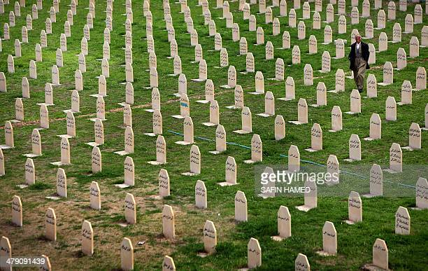 An Iraqi Kurd man walks past grave stones as he visits in a grave yard for the victims of a gas attack by former Iraqi president Saddam Hussein in...